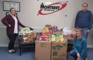 Director of Medical Records Operations Abbey Williamson, Team Lead Casey Eagy, and Case Auditor Jennifer Gardner pose with all food donated by Monterey Consultants